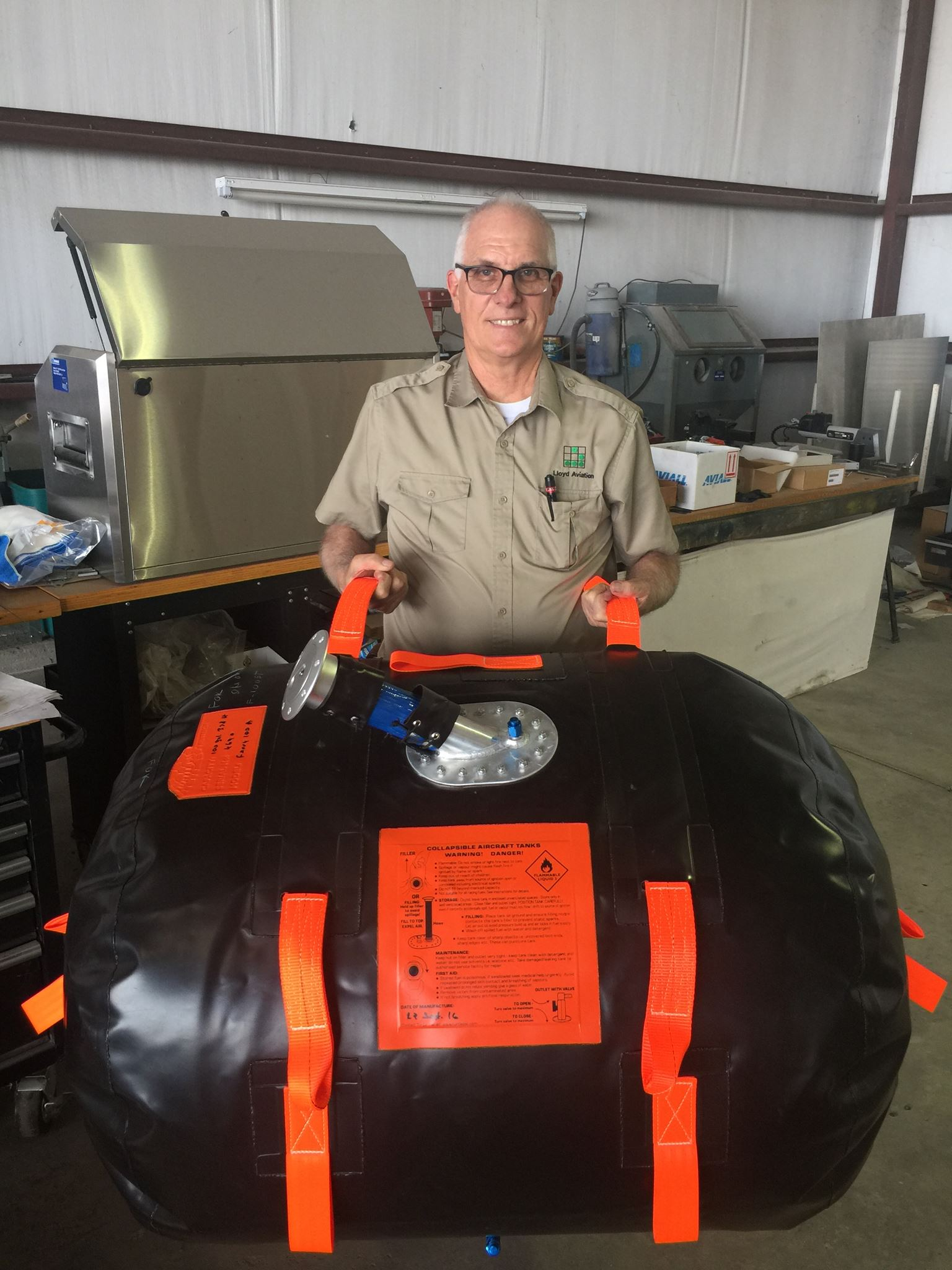 Brian Lloyd holds the extra 100 gallon fuel tank during installation in the Spirit airplane